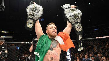 Conor McGregor in de octagon met zijn twee UFC titels