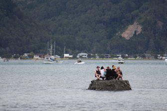 Groep mannen drinkend op een zelfgemaakt eiland in Nieuw-Zeeland om een alcoholverbod te omzeilen.